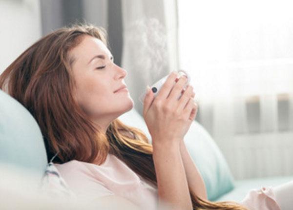 Женщина расслаблена, пьет чай