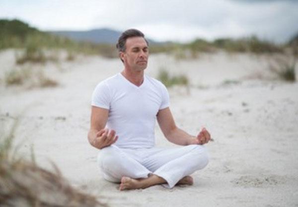 Мужчина медитирует на природе